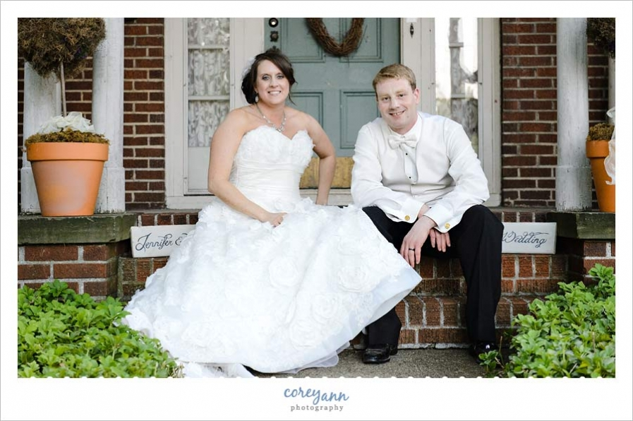 bride and groom sitting on steps in front of their new home