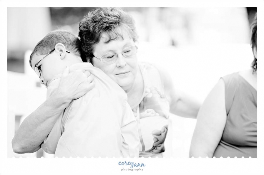 grandmother hugging grandson during wedding