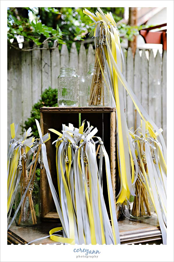 mason jars holding yellow and grey wands for waving after the wedding
