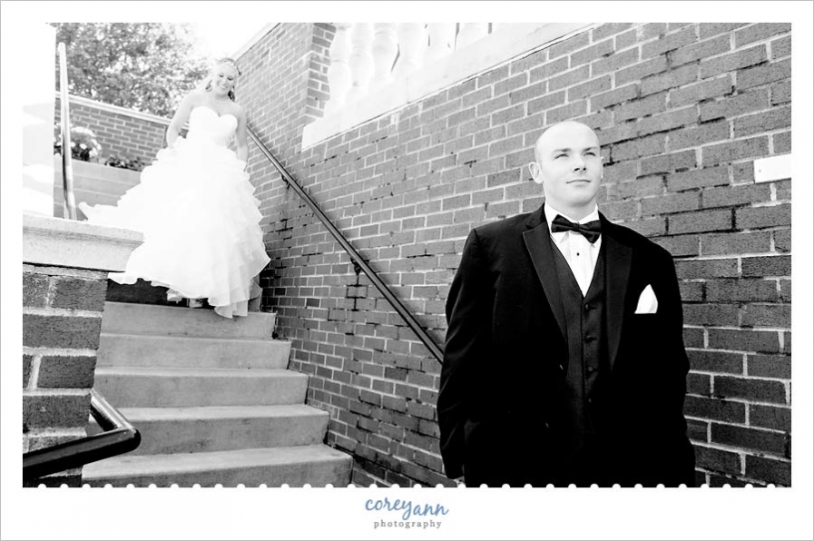 first look on stairs of bride and groom before wedding ceremony