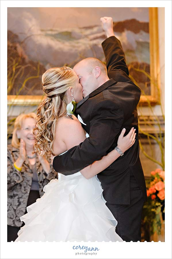 Groom raising fist during first kiss in wedding ceremony