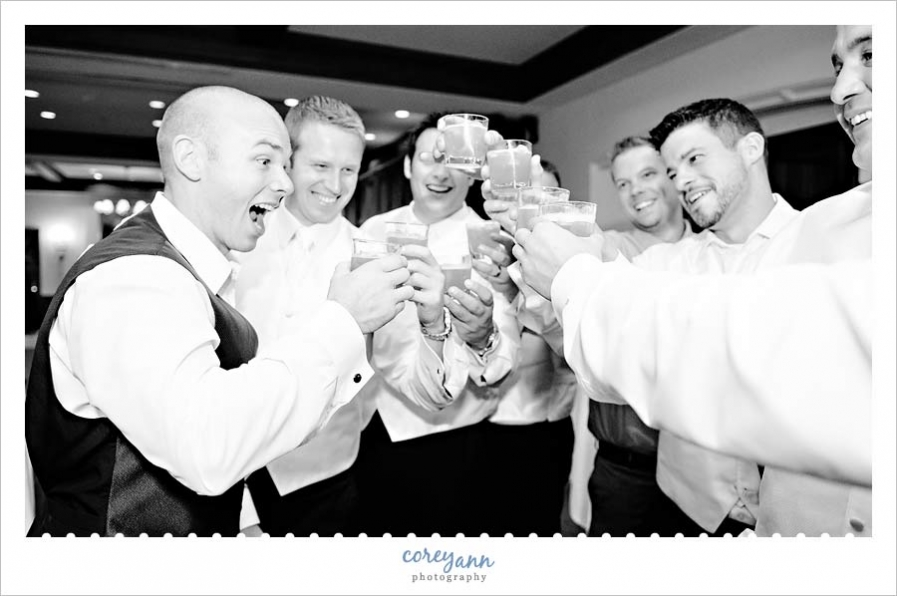 groom and groomsman doing a shot during wedding reception at portage country club