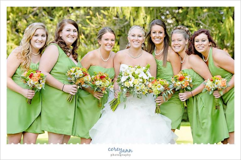 bridesmaids with green dresses and orange flower bouquets