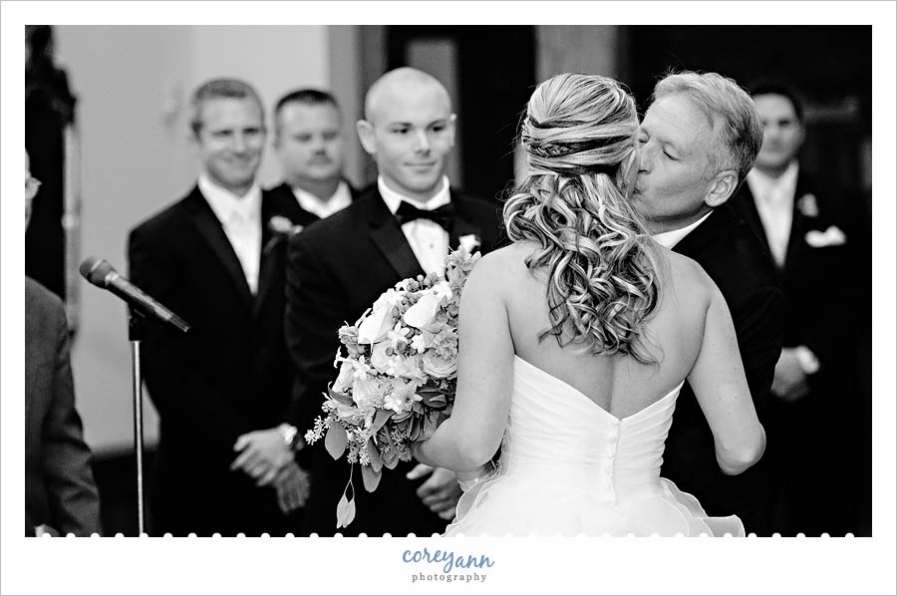 father of the bride kissing the bride when giving her away during wedding ceremony