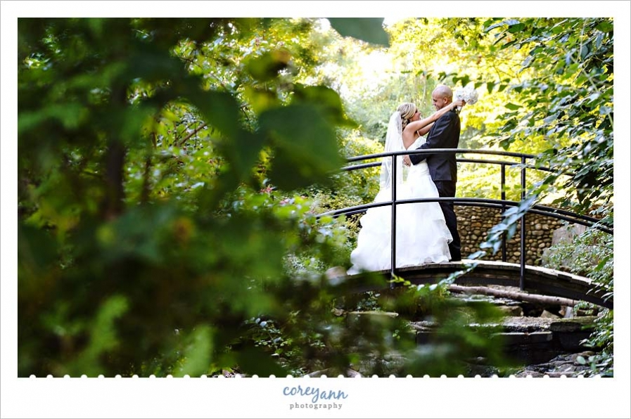 bride and groom posing on a bridge in a forest