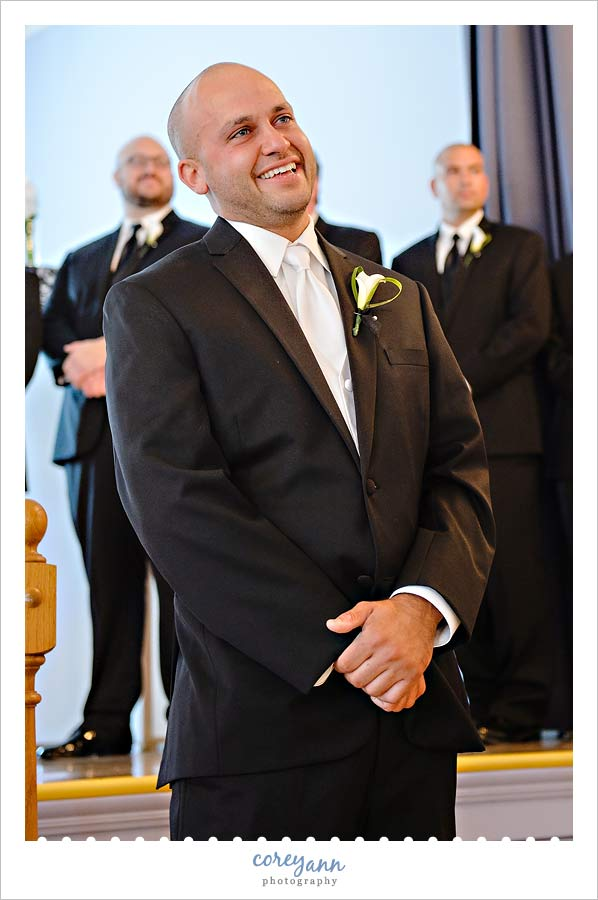 groom smiling when he sees his bride walking down the aisle
