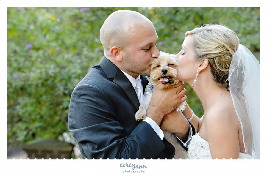 bride and groom posing with their dog after wedding