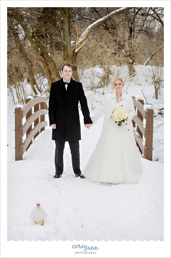 bride and groom posing outside with a duck