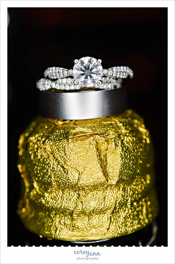 wedding rings on top of champagne bottle