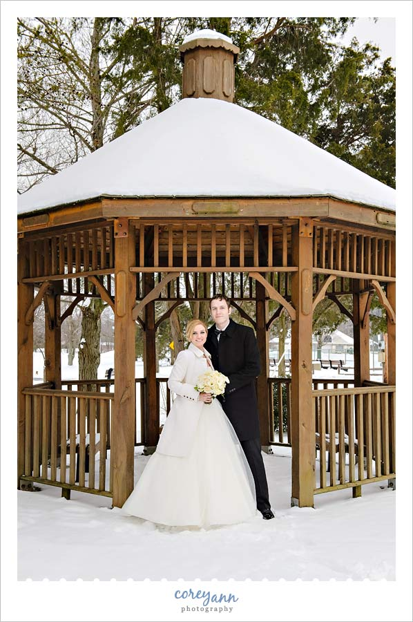 bride and groom outdoors in a gazebo covered with snow
