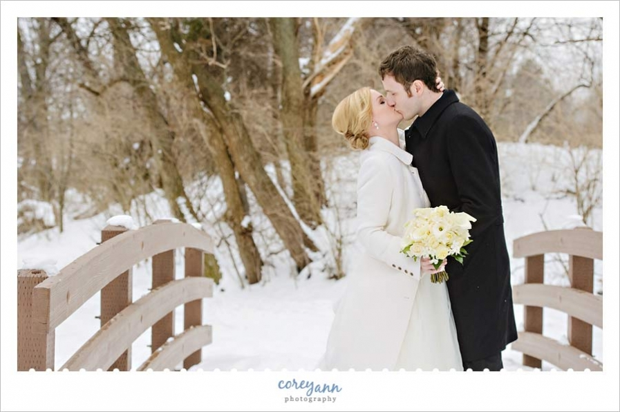 bride and groom kissing on a snow covered bridge in ohio