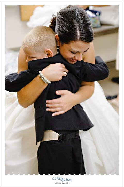 brides nephew giving her a hug before wedding ceremony