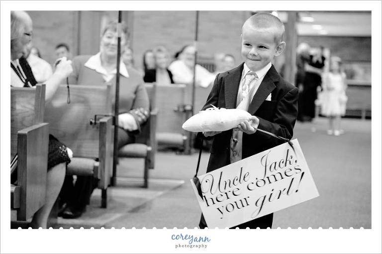 ring bearer carrying sign here comes your girl