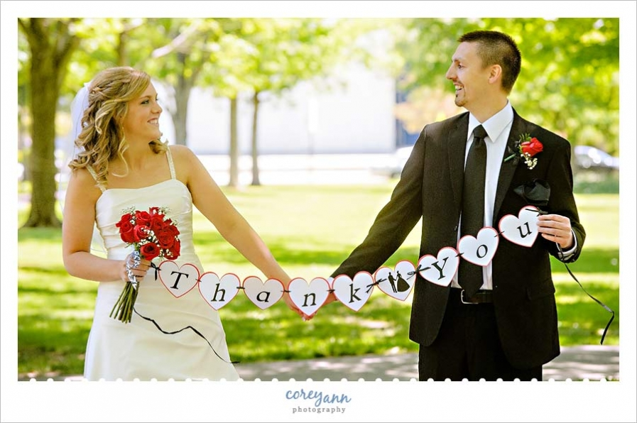 Bride And Groom Holding Thank You Sign