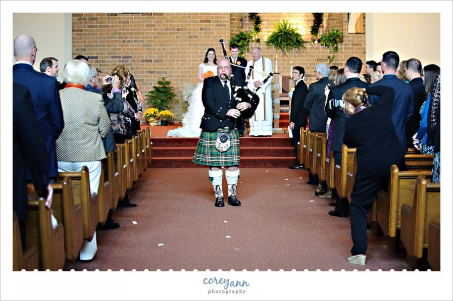 guest standing in aisle to take a picture during wedding ceremony