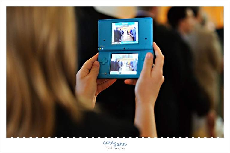 guest using nintendo ds to take pictures during wedding ceremony