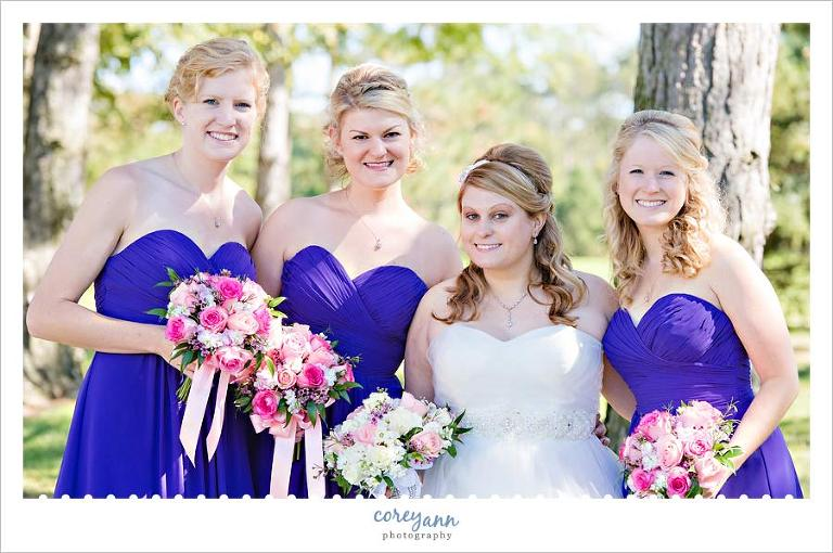 bridesmaids in purple dresses with pink bouquets