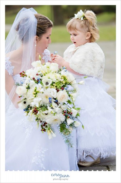 bride and flower girl playing with flower