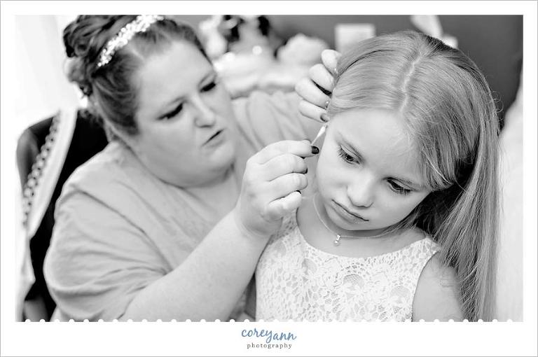 bride helping niece with earrings