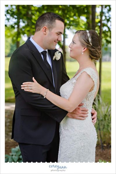 Bride and Groom pose outside for a wedding portrait in June