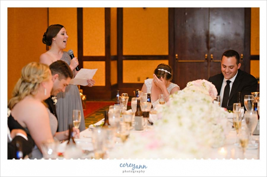 Bride and groom laughing during toast at wedding reception