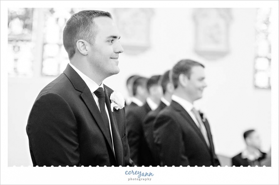 Groom smiling when seeing bride coming down aisle