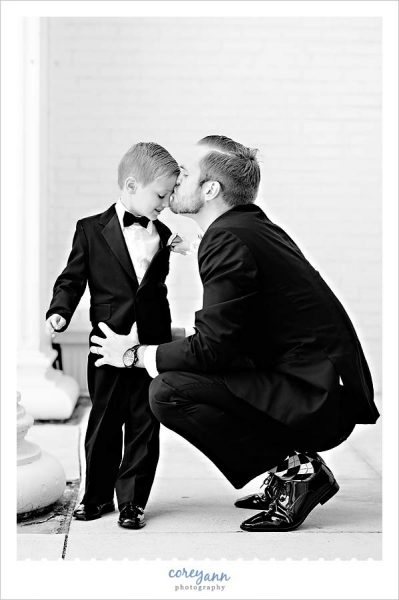 Groomsman kissing his son the ring bearer before wedding ceremony