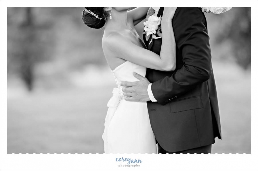 black and white wedding portrait of bride and groom kissing