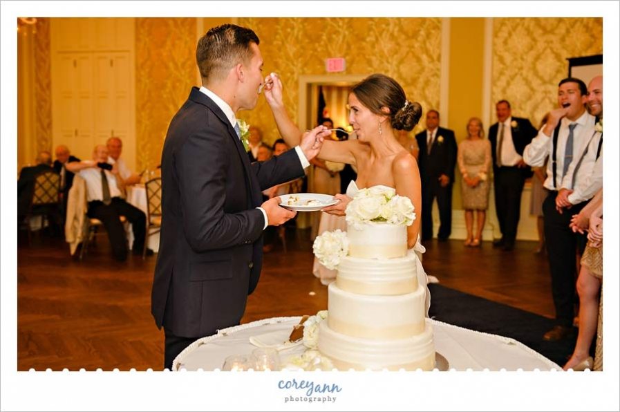 bride and groom eating cake at wedding reception