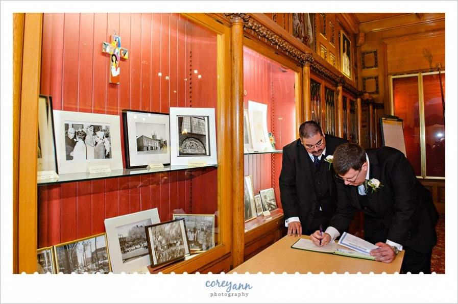 Grooms signing book for wedding ceremony