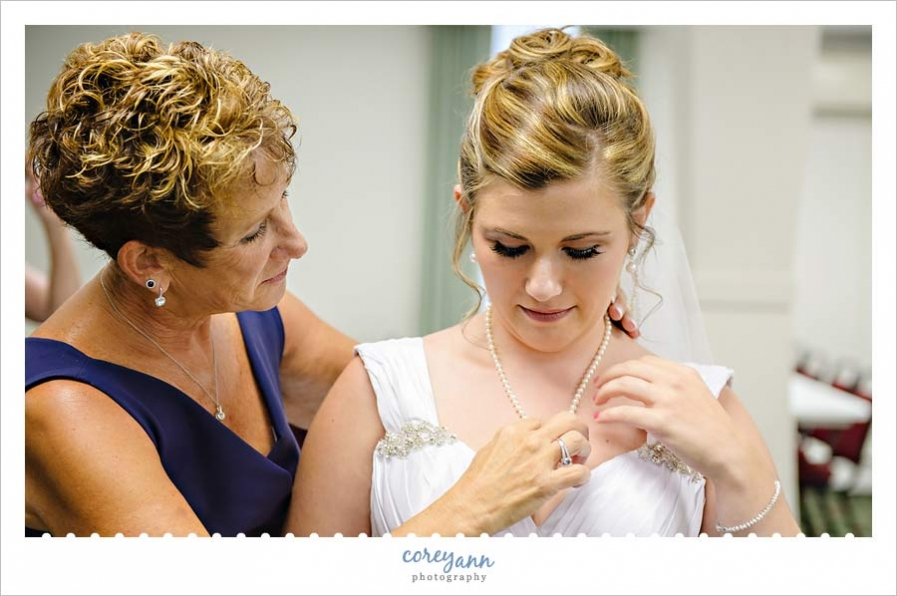 mother of bride helping bride get ready for wedding