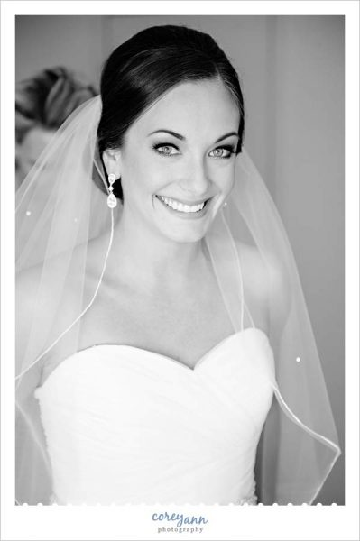 Bride smiling after getting veil placed in her hair
