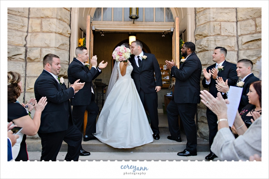 kissing while guests clap when exiting the church