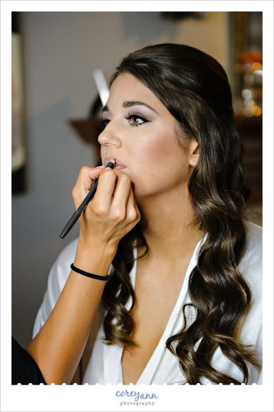 bride getting makeup done by makeup artist in akron ohio