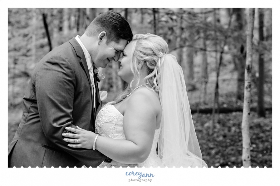 bride and groom touching noses in black and white photo