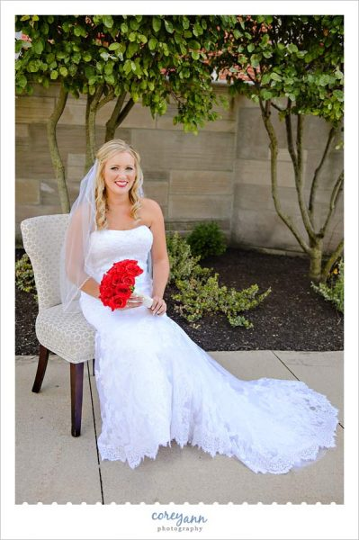 Bride seated in chair with red rose bouquet