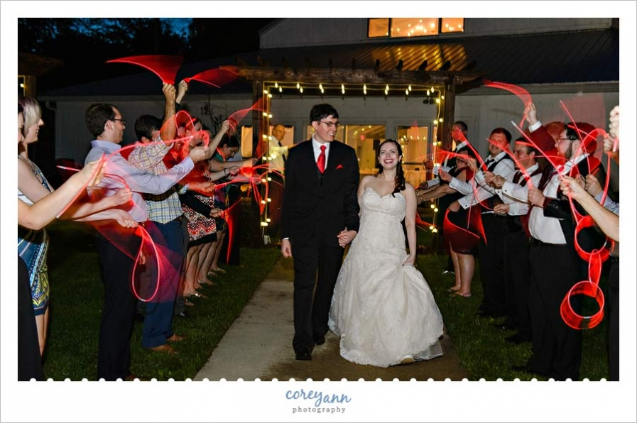 Bride and Groom Exiting with Red Glow Necklaces from Wedding Reception