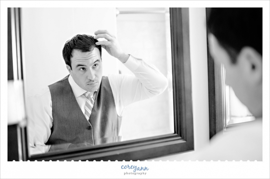groom fixing hair while getting ready for wedding