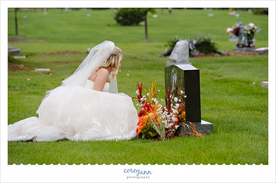 bride leaving bouquet at sisters grave after wedding