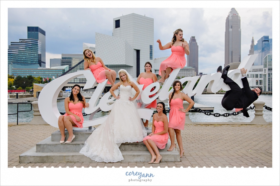 bridesmaids posing with bride on cleveland script sign