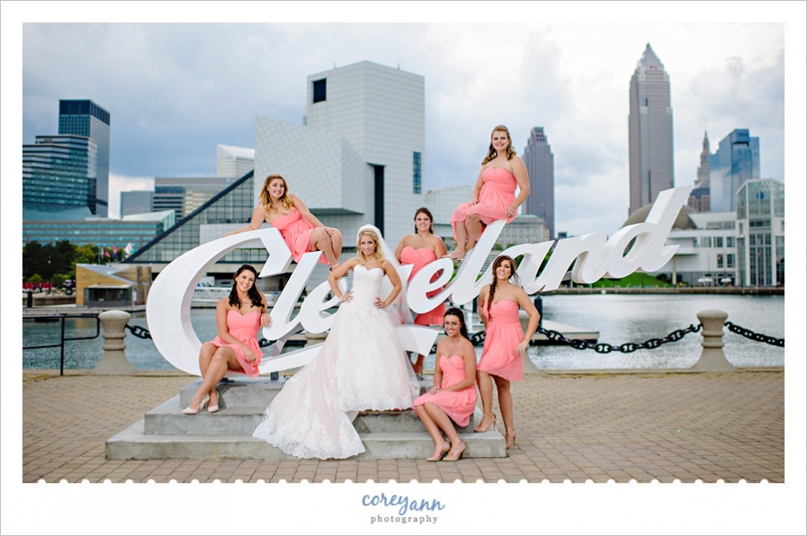 bridesmaids in short coral dresses posing with bride on cleveland script sign