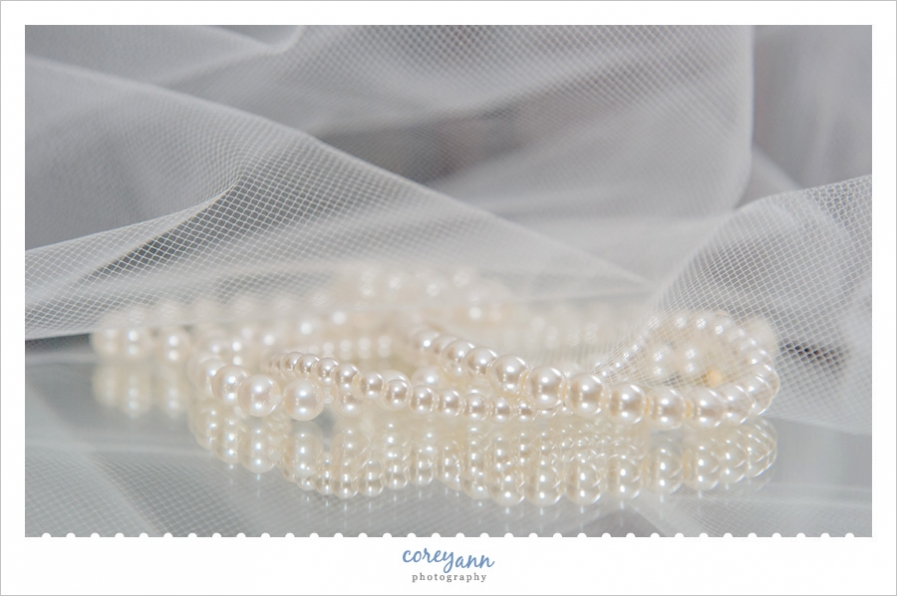 Wedding pearls sitting on a mirror with veil
