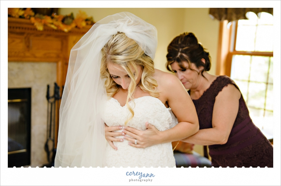 bride getting dressed while her mom helps her
