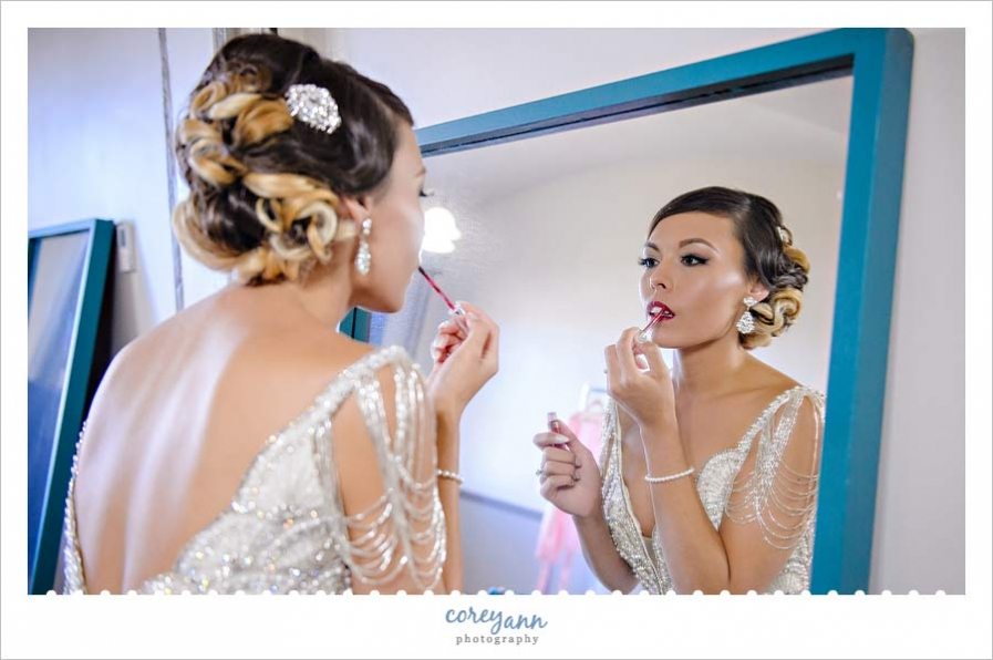 Bride putting on lipstick before first look