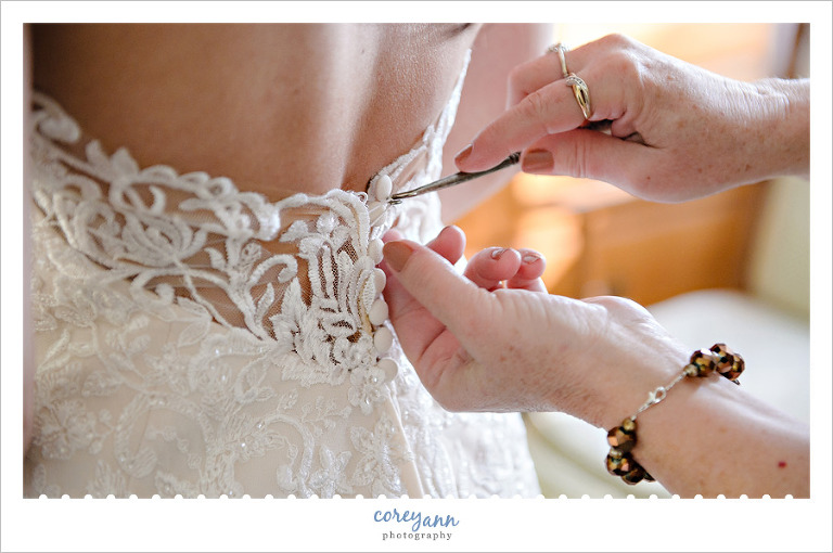 Bride's mother using button hook to do buttons on wedding dress