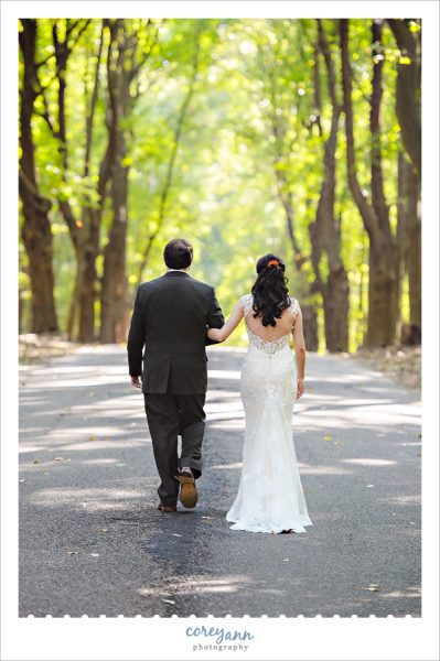 Bride and Groom walking along forest lined road