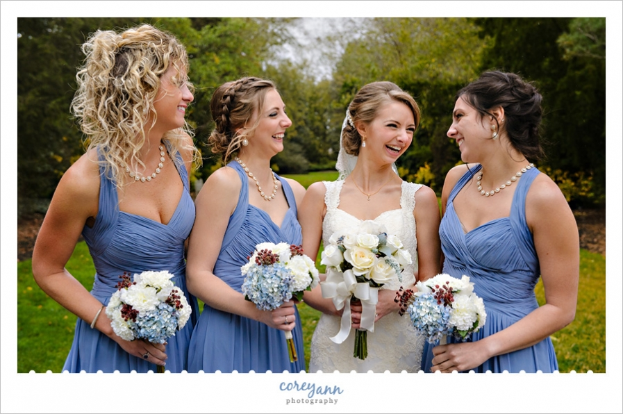 Bride laughing with bridesmaids in blue