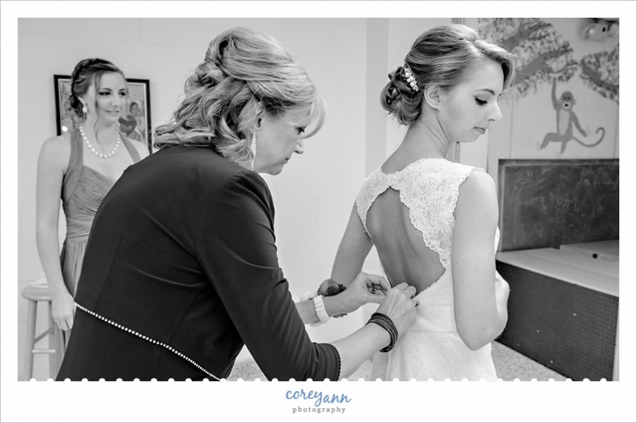 bride mother getting bride ready at st michael in canfield
