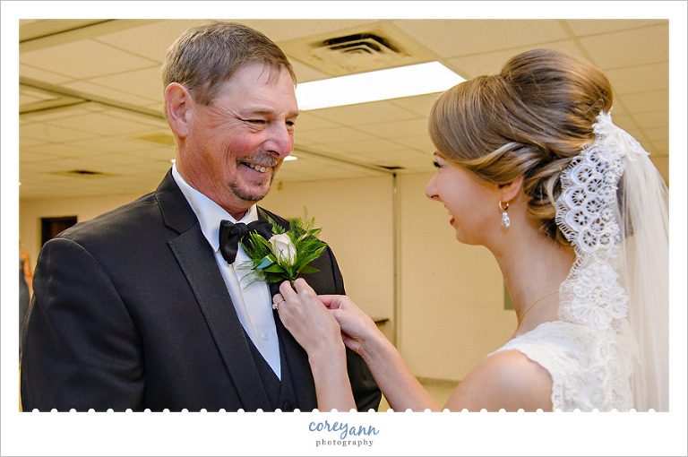 Bride pinning boutonniere on father before wedding