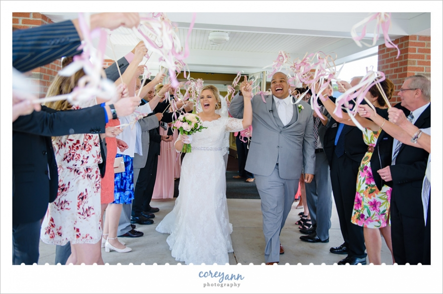Bride and groom exiting with ribbon wands